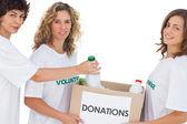 Volunteer women putting food in donation box — Stock Photo