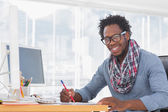 Smiling designer drawing with a red pencil on a desk — Stock Photo