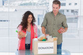 Volunteers taking out food from donations box — Stock Photo