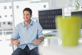 Cheerful photo editor in his swivel chair — Stock Photo
