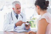 Doctor explaining the bottle of pills to patient — Stock Photo