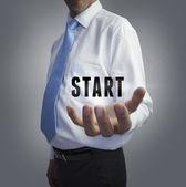 Businessman holding the word start — Stock Photo
