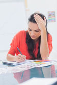 Overworked designer holding her head — Stock Photo