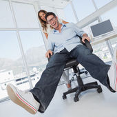 Smiling designers having fun with on a swivel chair — Stock Photo