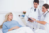 Hospitalized woman and doctors — Stock Photo