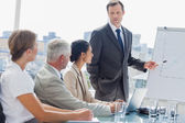 Zakenman wijzend op het whiteboard tijdens een vergadering — Stockfoto