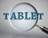 Magnifying glass showing tablet word — Stock Photo