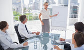Blonde businesswoman pointing at a growing chart — Stock Photo