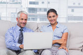 Business with laptop smiling at camera — Stock Photo
