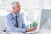 Doctor typing on his computer — Stock Photo