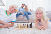 Children playing chess in front of their parents — Fotografia Stock
