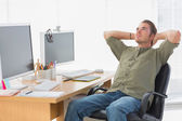 Handsome designer leaning back at his desk — Stock Photo
