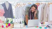 Smiling fashion designer using laptop — Stock Photo