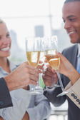 Business team celebrating with champagne and clinking glasses — Stock Photo