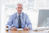 Attractive doctor sitting at his desk — Stock Photo