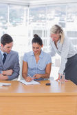 Businesswoman showing colleagues something with notepad — Stock Photo