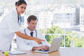 Doctor pointing at the laptop of a colleague — Stock Photo