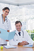 Smiling doctor showing a folder to a colleague — Stock Photo