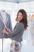 Attractive fashion designer measuring blazer lapel — Stock Photo