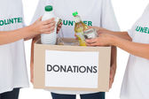 Group of volunteers putting food in donation box — Stock Photo