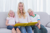 Portrait of a mother holding a story book with children — Stock Photo