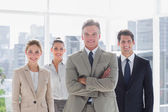 Boss with his arms folded standing with smiling colleagues behind — Stock Photo