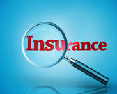 Magnifying glass revealing the word insurance written in red — Stock Photo