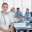 Stock Photo: Smiling woman doctor looking at the camera in front of her team