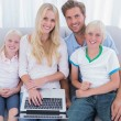 Stock Photo: Cheerful family using laptop in the living room