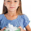 Portrait of a smiling little girl holding a wrapped gift — Stock Photo