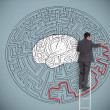 Businessman trying to solve a large maze with a brain illustration — Stock Photo #26990969