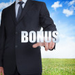 Businessman selecting bonus word — Stock Photo