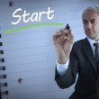 Businessman standing and writing the word start — Stock Photo #26991521