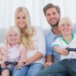 Family playing video games at home — Stock Photo #26991653