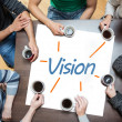 Team brainstorming over a poster with vision written on it — Stock Photo