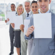Business team in a line holding white pages — Stock Photo #26991961