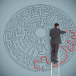 Businessman drawing red line to solve a maze — Stock Photo #26992103