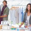 Fashion designers working and smiling at camera — Stock Photo