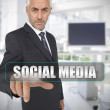 Businessman touching the term social media — Stock Photo #26992349