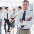 Boss standing with arms folded in a modern office — Stock Photo #26992495