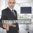 Stock Photo: Businessmtouching term exceed expectations