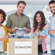Smiling team of volunteers taking out clothes from a donation box — Stock Photo #26992575