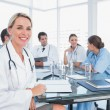 Blond doctor sitting next to her medical team — Stock Photo