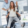 Stock Photo: Cheerful designers having fun with swivel chair