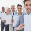 Business team in a line holding blank pages — Stock Photo #26993065