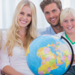 Family sitting on couch holding globe — Stock Photo
