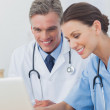 Two cheerful doctors working on a laptop — Stock Photo