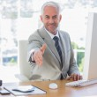 Smiling businessman reaching out arm for handshake — Stock Photo