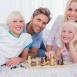 Smiling family playing chess together — Stock Photo