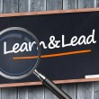 Learn and lead written on a blackboard — Stock Photo